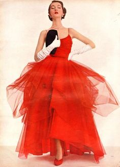 1950s model Dovima in a red tulle evening dress and white elbow length gloves. 1950s fashion images.