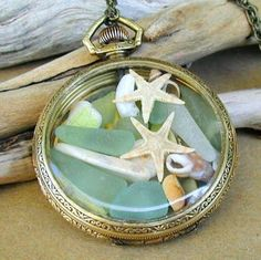 Seaglass and shells in old pocket watch. ornaments?