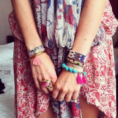 Layers of brightly coloured woven friendship bracelets and statement rings | relaxed bohemian styling.