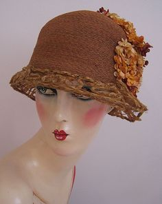 Art Deco, 1920s Flapper Hat, Cloche Silk Flowers and Jewels. This is an amazing Art Deco, 1920s cloche hat. It is so elegant! This hat is made of fine, tightly woven rows of silk braid in a deep peach color. The hat has a crown of pink and peach colored flowers caught with a large rhinestone, jewel set, metal ornament. There are silk fuzzy flower centers in the largest of the flowers near the jewels.