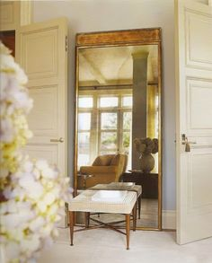 Flank bookcase with large gilt edged mirrors.  Create aged mirror with mercury process.
