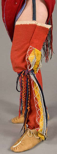 """Wôbanaki Women's 1800 - This woman wears a sash around her waist & garters, called """"kiganibial"""", tied on just under her knees. The finger woven garters help to keep the woman's leggings in place.These are wool leggings, called """"medasal"""". They are tied to a belt at the waist to keep them up. Leggings were worn for warmth and to protect one's legs when walking through scratchy undergrowth. These leggings have been decorated with ribbons and white glass beads, all received in trade."""