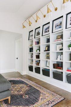 Hardwood floors covered in a red and black kilim rug lead to a wall lined with built in bookshelves accented with gray painted backs featuring charcoal gray woven baskets on the lower shelves and perfectly sized black framed photographs on the upper shelves lit by brass Boston function library wall lights.