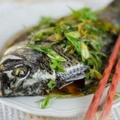 A Cantonese steamed fish recipe topped with scallions, ginger, soy and hot oil.