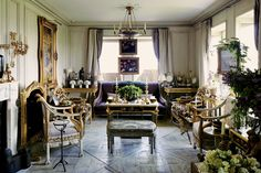 """Howard Slatkin refers to the narrow living room as the """"bowling alley."""" To compensate, he stained the dark parquet floors a pale gray to match the walls and open up the space. The curtain hardware is from P. E. Guerin. (Photo: Simon Watson)"""