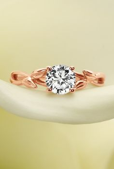 Wispy vines and delicate buds of warm rose gold entwine toward a brilliant center diamond in this nature-inspired ring.