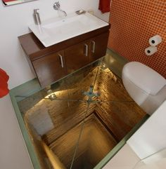 Bathroom with glass floor built over an elevator shaft. Crazy!
