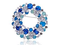 Beautiful wreath. Made from fine genuine sapphire blue, pacific opal, and clear Swarovski crystal rhinestones. Each high quality crystal is hand faceted and checked for clarity and brilliance. Hand crafted using the highest quality shiny polished silver tone metal alloy. This fine piece of art jewelry makes for the perfect gift for that someone special.