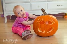 Baby's first Halloween with hands and feet carved into the pumpkin.