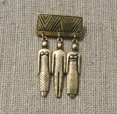 You dont see this brooch often! Laurel Burch golden Man Woman Brooch. Measures 1 1/4 of an inch across. Total length is 2 1/4 inches.  No condition