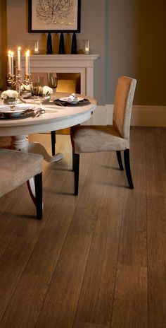 Sophisticated dining room featuring Colonia Virginia Walnut luxury vinyl tile flooring with Walnut marquetry strip in ships decking design