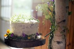 Lovely homemade wedding cake presented on a timber slab with wild flowers. So pretty.