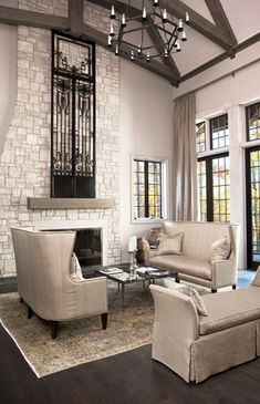 Drapes set 18 inches taller than window, interesting couches.  photo- limestone-fireplace and 19th Century iron door from Italy