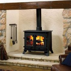 Woodburning stove suppliers for Wiltshire for the supply and installation of quality woodburning stoves such as this classical stone fireplace design and two door stove. Brick Fireplace Makeover, Inglenook Fireplace, Small Fireplace, Stove Fireplace, Wood Fireplace, Fireplace Design, Fireplaces, Hanging Fireplace, Fireplace Tools