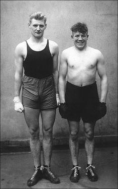 Podemos observar, nesta foto, dois atletas, bastante contentes. As suas vestes aparentam ser muito simples, mostrando a maneira como se vestiam para uma competição.