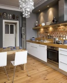 Wood floors, wood counters, brick wall, grey paint, white kitchen & white chandelier. Love.