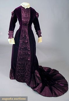"""PURPLE VELVET TRAINED GOWN, LATE 1870s. 1-piece royal purple silk velvet w/ shirred satin bands at center front, center back & on sleeves above lace cuff flounces, fan shaped satin inserts trim long train, hook & eye front opening, upper sleeve slashed w/ satin inserts,"" Augusta Auctions"