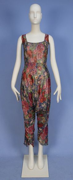 TURKISH INSPIRED SILK and LAME EVENING COSTUME, c. 1920. Imported by Mme. Najla Mogabgab, sleeveless 1-piece jumpsuit of floral printed chiffon having silver metallic threads, bodice shaped with vertical darts and arcing high waist, the legs gathered and tapered in the Turkish style, lined in cream silk, side closure. Labeled. B-40, W-34, H-44, L-55. Excellent. $720.