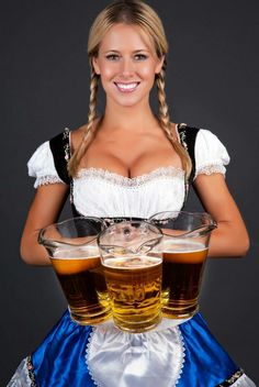 German barmaid in braids wearing dirndl and holding pitchers of beer.