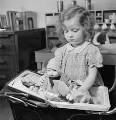 Jacqueline (aged 3) is an evacuee from Luxembourg to Surrey. Here we see her playing with her doll and doll's pram at the house in which she is staying, somewhere in Surrey. 1942.