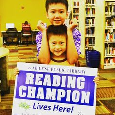 We're so proud of our #ReadingChampions at the library who have completed the #SummerReadingClub challenge. And not only was this little guy proud of his efforts, his older brother was proud of him too. #AbilenePublicLibrary #Reading #Summer #ReadingChallenge #YardSigns #Kids #Youth #Brothers #Siblings #Smile