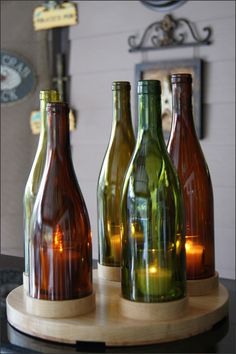 Wooden Stand Wine Bottle Round Candleholder - The colors of the glass add an ambiance great for an indoor table centerpiece, mantel display, wine bar, or a patio or porch area. The bottles sit on a 3/4  (+/-) wood base with wooden feet. Each bottle fits into its own individual stand.  http://woodsmithofnaples.com/wooden_stand_wine_bottle_candleholder.html