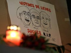 A drawing depicting cartoonist Jean Cabut, left, Charlie Hebdo editor Stephane Charbonnier, center, and cartoonist Georges Wolinski, is placed outside the French Embassy in Berlin, Germany. The message reads 'Victims of their success, R.I.P.'