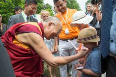 His Holiness the Dalai Lama greeting a young well-wisher as on his arrival at Wiesbaden Kupark in Wiesbaden, Hessen, Germany on July 12, 2015. Photo/Manuel Bauer