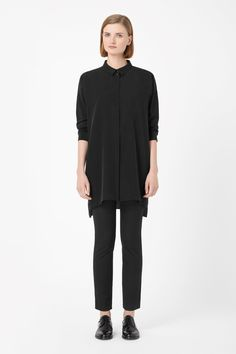 Made from lightly textured silk, this elongated shirt is wide-cut for a loose, oversized fit. A long-sleeved style, it has a narrow pointed collar, graduated hemline and a hidden front button fastening.