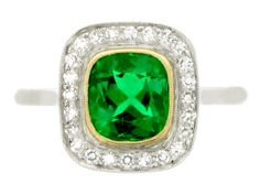 Emerald and diamond cluster ring, circa 1920. A yellow gold and platinum ring set with one central cushion shaped old cut untreated Muzo emerald in a yellow gold millegrain collet setting with an approximate weight of 1.20 carats, encircled by a conforming single row of twenty four round eight cut diamonds in platinum millegrain bead settings with an approximate total weight of 0.35 carats, all above an openwork gallery set with hearts and cheniers, with raised inward tapered shoulders, all…