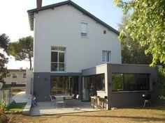 Extension gris foncé en contraste avec la maison blanche