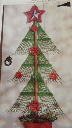 Upcycled yard rakes made into a Christmas tree with water faucet handles for decoration.