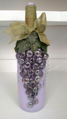 Large wine bottle painted a light purple. with jeweled grape design.