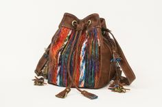 Bolsa saco com franjinhas laterais removíveis, confeccionada em couro ecológico e trabalho artesanal em lã ao centro. Nas costas, o meio é em couro ecológico, possibilitando usá-la toda lisa. CONSULTAR DISPONIBILIDADES DE CORES E ESTAMPAS!!! PRODUTO TOTALMENTE EXCLUSIVO!!! R$ 210,00