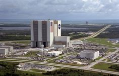 https://flic.kr/p/fqmChV | Aerial View of Launch Complex 39 | An aerial view of the Launch Complex 39 area shows the Vehicle Assembly Building (center), with the Launch Control Center on its right. On the west side (lower end) are (left to right) the Orbiter Processing Facility, Process Control Center and Operations Support Building. Looking east (upper end) are Launch Pads 39A (right) and 39B (just above the VAB). The crawlerway stretches between the VAB and the launch pads toward the…