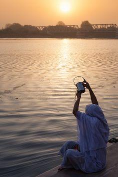 Hindu woman doing her evening puja by the holy Yamuna river in Mathura, Uttar Pradesh, India.