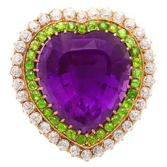 Amethyst, diamond, and demantoid garnet heart-shaped brooch,displaying the suffragette colors. Mounted in gold, this pin can also be worn as a pendant.