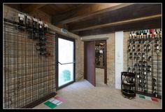 Una porta dotata di maniglione antipanico in una cantina per il ricovero dei vini. Una struttura dal design semplice ed originale per contenere tutte le bottiglie.