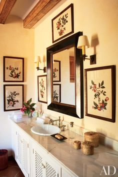 In this Spanish guest bath by Michael S. Smith, framed textiles mingle with Robert Kime sconces and a mirror by HomArt. Read on for more guest bathroom decoration inspiration.