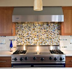 Smaller mosaic tiles just behind stove, with larger, more neutral tiles under cabinets. Great notes in installation.