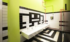 the interior uses a bright palette of black and white tiles to create a cost-effective sense of identity and playfulness within the educational facility.