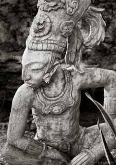 Statue of an ancient Mayan warrior in a jungle setting in Mexico's Riviera Maya region. © David A. Kamm