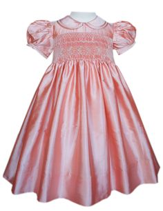 This is a beautiful Peach flower girl dress. Hand smocked in the bodice are peach flowers. There is a Peter Pan collar and puffy sleeves both of which are edged with fagoting. It also has covered buttons on the back as well as a tying sash. The skirt is lined and this dress is shimmering!