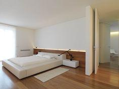 Camera de letto moderna minimal, con particolare illuminazione lungo la cornice e lampade da comodino con braccio flessibile, perfette per leggere