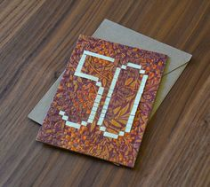 on this card i've folded strips of paper to make the number fifty