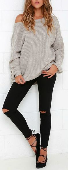 Chic blonde in black ripped jeans and grey oversized sweater