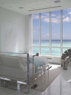 All white room with clear headboard and all glass wall with ocean front view