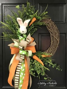 "This grapevine wreath is adorned with a fluffy bunny, carrots, mixed grasses and large beautiful bow. (Exact ribbon style and colors may vary due to available inventory) This wreath is built on a 18"" round grapevine."