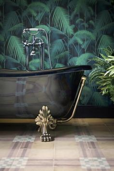 Copper clawfoot rolltop bath and Cole & Son Palm Jungle wallpaper in the bathroom at The Corner Townhouse in Rome, Italy.