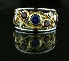 14k two tone ring was custom fabricated and hand made with sapphires, diamonds and garnets bezel set in a wide band with fillagree accents